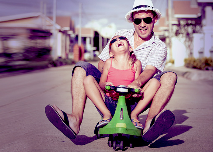 Home Insurance for a father and his little daughter on a green toy scooter